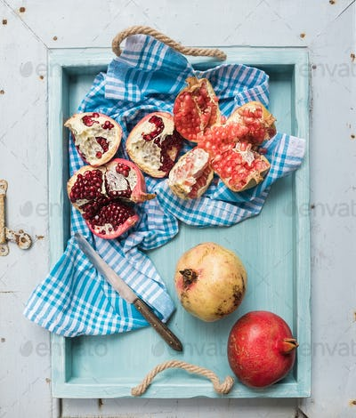 Red and white pomegranates with knife on kitchen towel