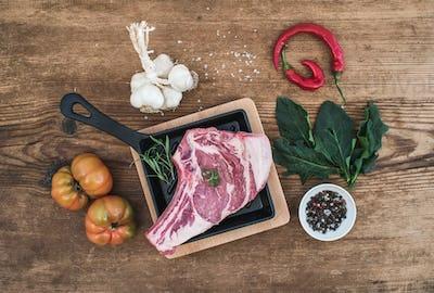 Raw fresh meat ribeye steak with pepper, salt, chili, heirloom tomatoes and rosemary