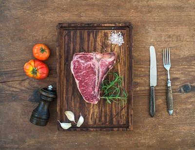 Raw fresh meat t-bone steak with garlic cloves, tomatoes, rosemary, pepper and salt