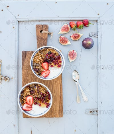 Healthy breakfast set. Bowls of oat granola with yogurt, fresh strawberries, figs, pomegranate
