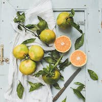 Fresh Turkish tangerines with leaves over blue rustic wooden backdrop, top view.