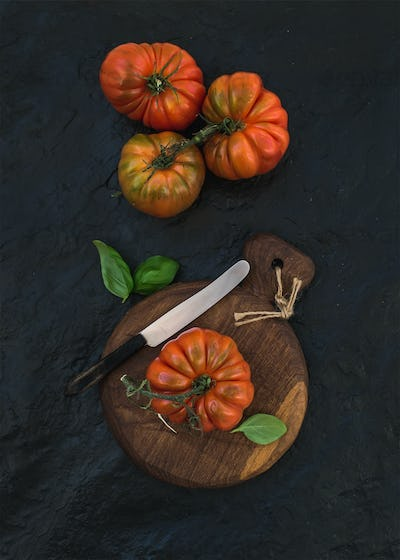 Fresh ripe hairloom tomatoes and basil leaves on rustic wooden board over black stone background.