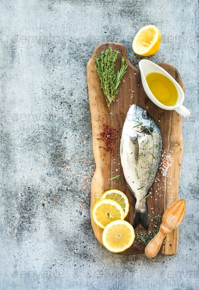 Fresh uncooked dorado or sea bream fish with lemon, herbs, oil and spices
