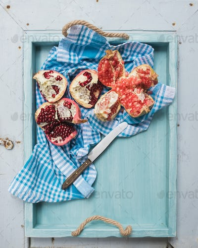 Red and white pomegranates with knife in blue tray over light painted wooden backdrop