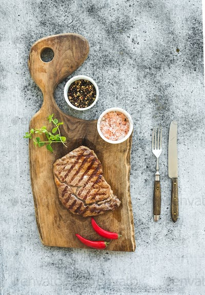 Grilled ribeye beef steak with herbs and spices on walnut cutting board over grunge grey background