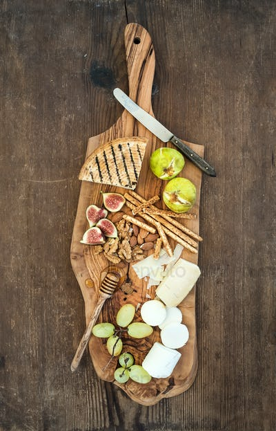 Wine appetizers set: cheese selection, honey, grapes, almonds, walnuts, bread sticks