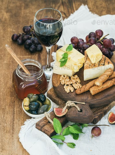 Glass of red wine, cheese board, grapes, fig, strawberries, honey and bread sticks
