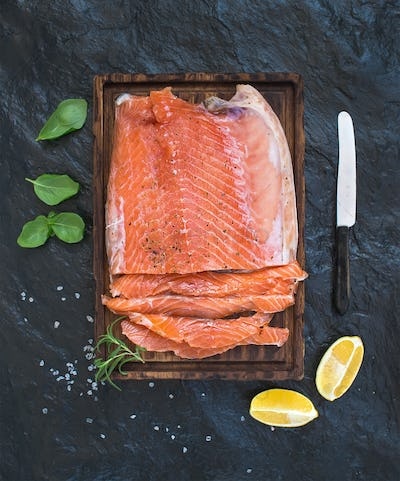 Smoked salmon filet with lemon, fresh herbs and bred on wooden serving board