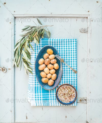 Green big olives in rustic ceramic plate with tree branch and spices