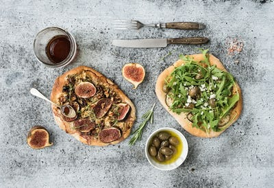 Rustic homemade pizzas with eggplant, cheese, olives, arugula, prosciutto and figs