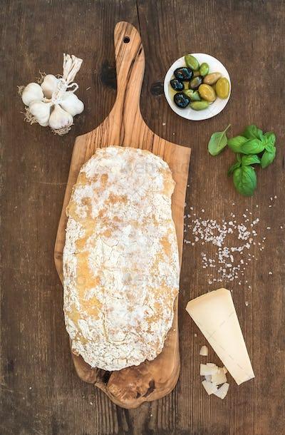 Freshly baked ciabatta bread with garlic, mediterranean olives, basil and Parmesan cheese
