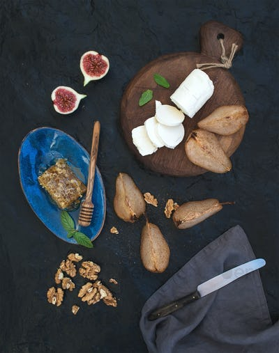 Appetizer set. Roasted pears, goat cheese on rustic dark wooden board