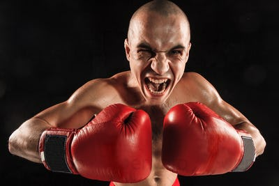 The young man kickboxing on black  with screaming face