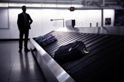 Businessman waiting for suitcase on luggage conveyor belt, airpo