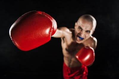 The young man kickboxing on black  with kapa in mouth