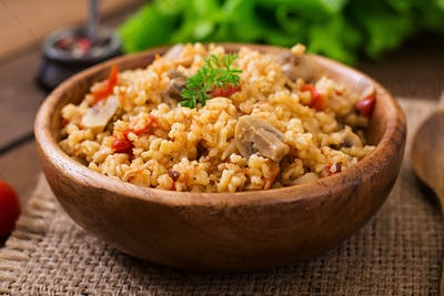Bulgur with chicken, mushrooms and tomatoes in a wooden bowl. Top view