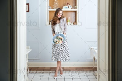 Cheerful woman standing in cafe and holding bouquet of flowers