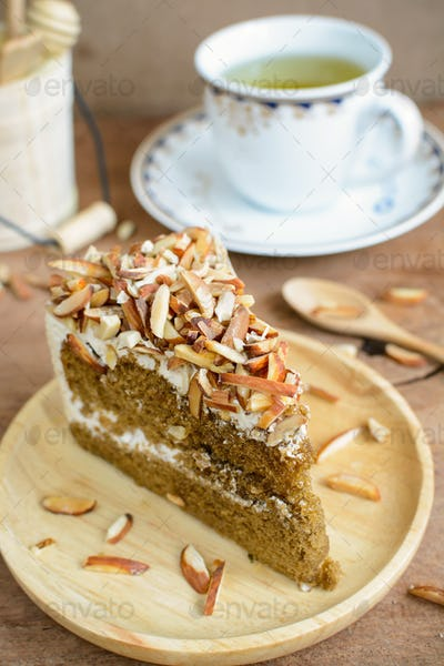 Coffee cake with almonds on top and cup of tea