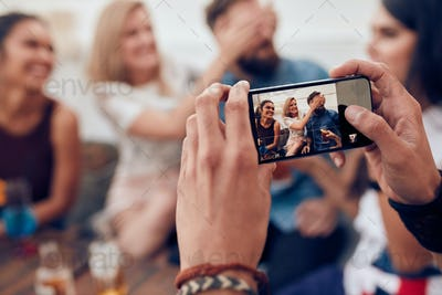 Photographing friends at party with mobile phone