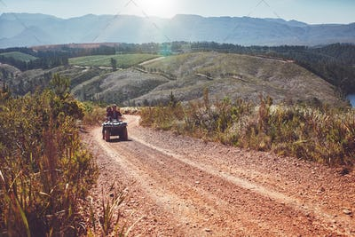 Young couple riding quad bike on country road