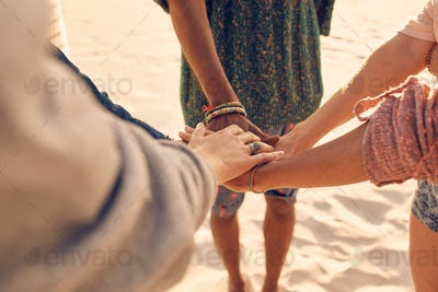 Friends at the beach putting hands together