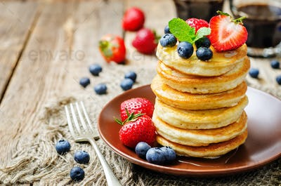 pancakes with honey, strawberries and blueberries