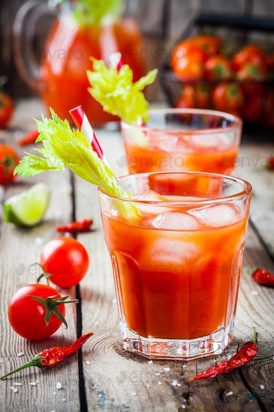 tomato juice with celery and ice in glasses