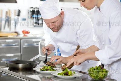 Smiling professional chef prepare steak dish at restaurant