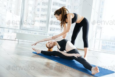 Cheerful woman doing split and exercisings with her coach