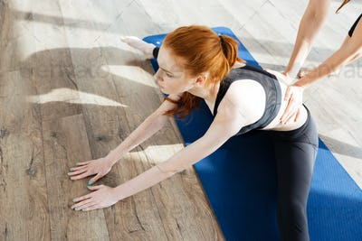 Young woman training and stretching with trainer
