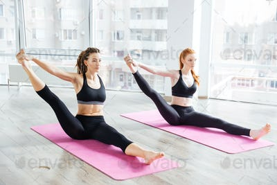 Two women stretching legs and practicing yoga in studio