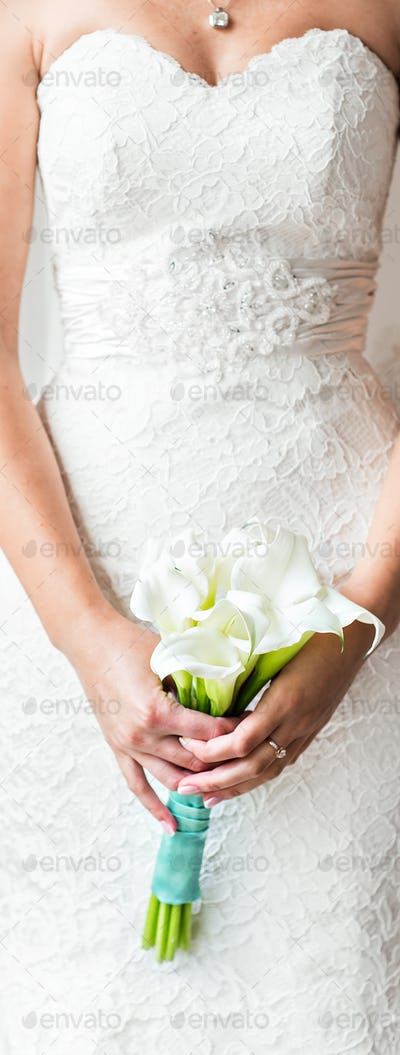 bride holding a bouquet of white callas