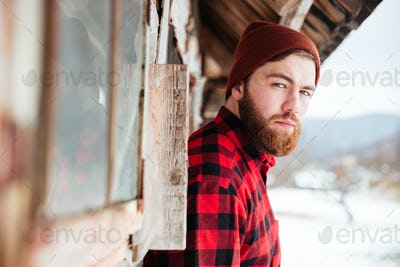 Serious man in old wooden house at village