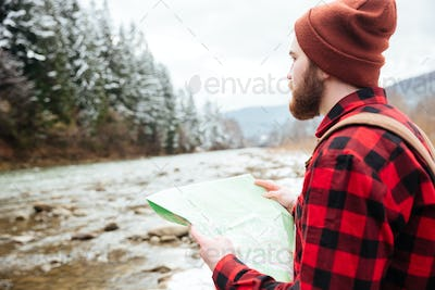 Male hiker holding map outdoors