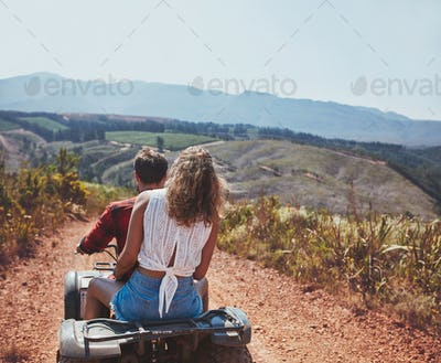 Young couple riding on a quad bike in countryside