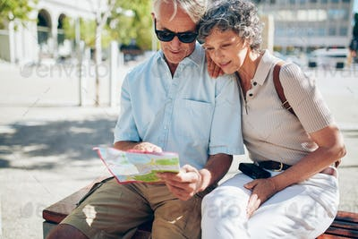 Senior couple looking for a destination on a city map
