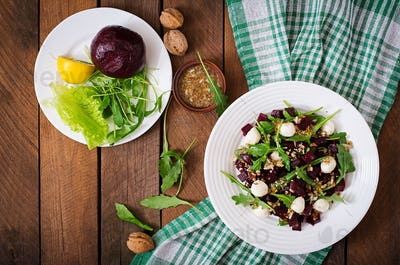 Salad of baked beets, arugula, cheese and nuts. Top view