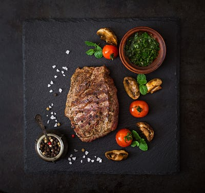 Juicy steak medium rare beef with spices and grilled vegetables. Top view