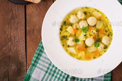 Dietary soup with chicken meatballs and stalks of celery. Top view