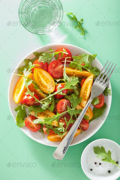 tomato salad with arugula over green background