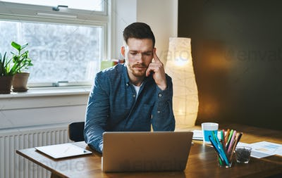 Worried entrepreneur young man working at desk