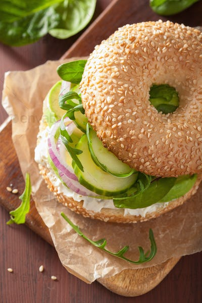 avocado sandwich on bagel with cream cheese onion cucumber arugu