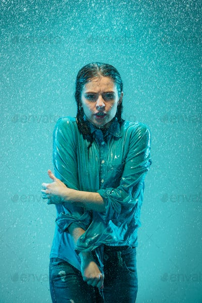The portrait of young beautiful woman in the rain