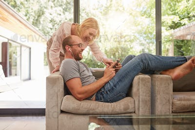 Mature couple at home using digital tablet