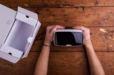 Hands of man holding virtual reality goggles, wooden table