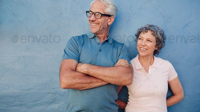 Smiling mature couple standing together and looking away