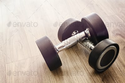Dumbbells on wooden floor in gym