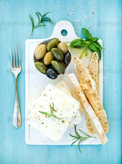 Fresh feta cheese with olives, basil, rosemary and bread slices
