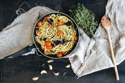 Pasta spaghetti with pesto sauce, basil, cherry-tomatoes, garlic and thyme