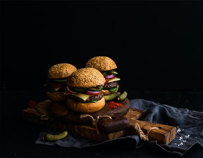 Fresh beef burgers with pickles and spices on rustic wooden boards, black background.